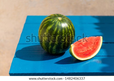 Whole and sliced baby watermelon on the blue wooden table france Stock fotó ©