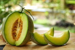 Whole and sliced of Honeydew melons,honey melon or cantaloupe (Cucumis melo L.) on wooden table with blurred garden background.Favorite fruit in summer.Food,Fruits or healthcare concept.