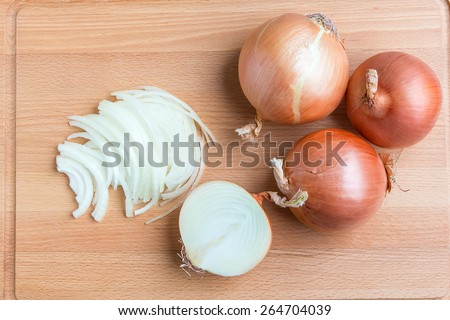 Whole and sliced onions on wooden cutting  board.