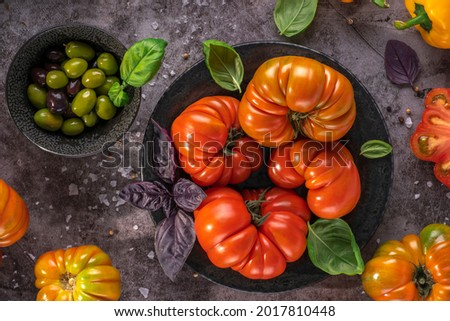 Whole and sliced organic tomatoes Raf Coeur De Boeuf. Raw fresh tomatos with sea salt and basil and olives in plates on rustic dark metal texture background Zdjęcia stock ©