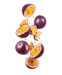 Whole and sliced ripe passion fruit in the air, isolated on a white background