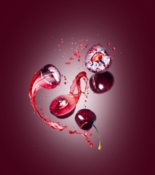Whole and sliced sweet cherries with splashes of juice on a red background