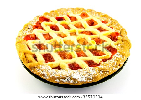 Whole apple and strawberry pie on a black plate on a white background