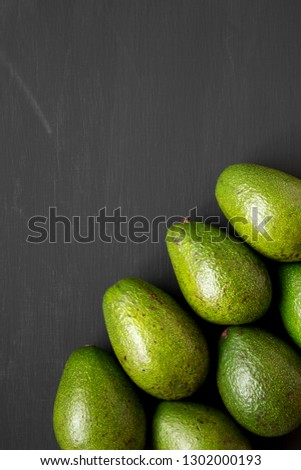 Whole avocados on black wooden surface, top view. Overhead, overhead, flat lay. Space for text. #1302000193