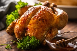 Whole baked chicken with crusty skin glazed with honey on top and parsley on the side.