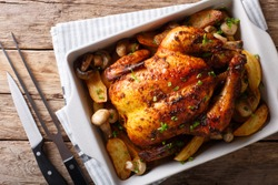 Whole baked chicken with mushrooms and potatoes close-up in a baking dish on a table. horizontal top view from above