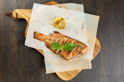 whole baked fish in foil with lemon. fried bass