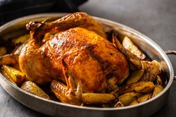 Whole baked golden crispy chicken in a pan cooked with potatoes.