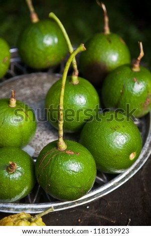 Whole ball avocados on a metal plate - stock photo