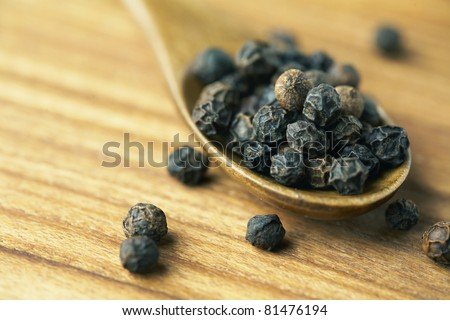 Whole black pepper on wooden spoon.
