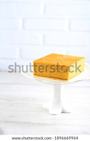 Whole Cake Full Square Plain Indonesian Layer Cake or Lapis Legit on Cake Stand, White Concept for Homemade Bakery Foto stock ©