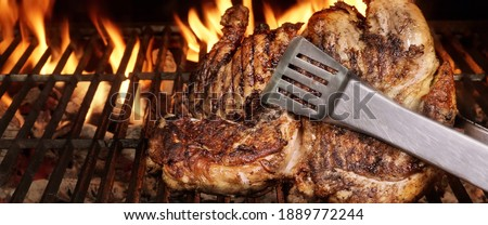 Whole Chicken Grilled On Hot Barbecue Charcoal Flaming Grill. Juicy Chicken Meat Roasted on BBQ Grill. Backyard Grill Party Dish From Poultry Isolated On Black Background, Closeup View.