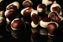 Whole chocolates in seafood shapes on black background with reflection