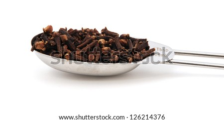 Whole cloves measured in a metal tablespoon, isolated on a white background