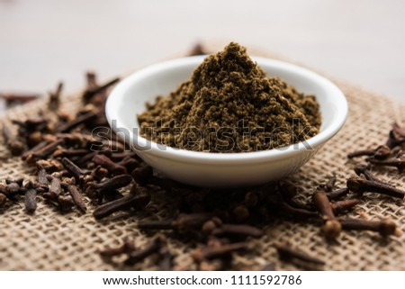 whole Cloves or laung or lavang with powder in a bowl isolated on white. Whole cloves. Selective focus #1111592786