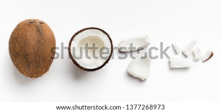 Whole coconut and pieces of coconut on white background, top view