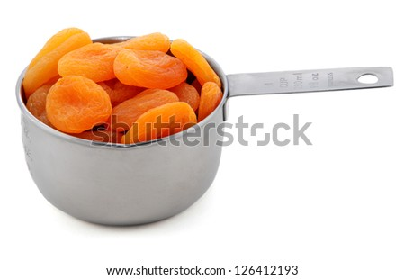 Whole dried apricots presented in an American metal cup measure, isolated on a white background