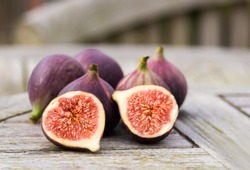 Whole figs and one fig sliced in half on top of a teak garden table. Focus is on the sliced fig.