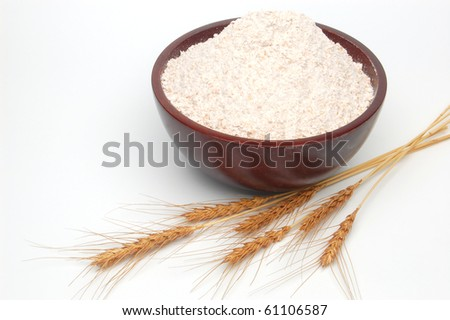 Whole flour in bowl with wheat ears on white