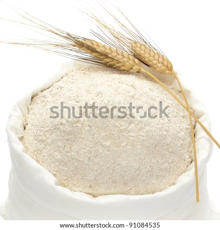 Whole flour with wheat ears on white background
