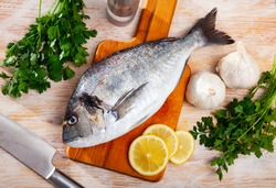 Whole fresh gilthead bream on wooden surface with vegetables, lemon and spices ready for cooking