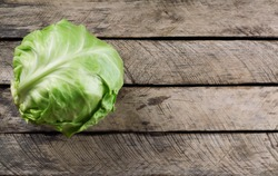 whole fresh green cabbage on wooden background . Top view