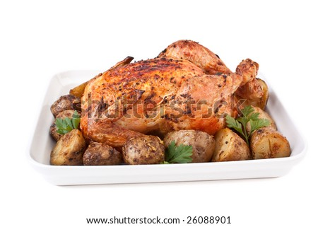 Whole golden roasted chicken with roasted potatoes and parsley isolated