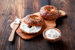 Whole grain bagels with cream cheese on wooden board, selective focus