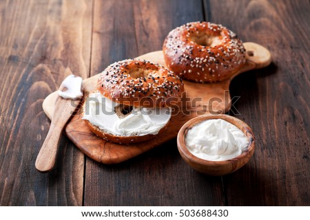 Shutterstock Whole grain bagels with cream cheese on wooden board, selective focus