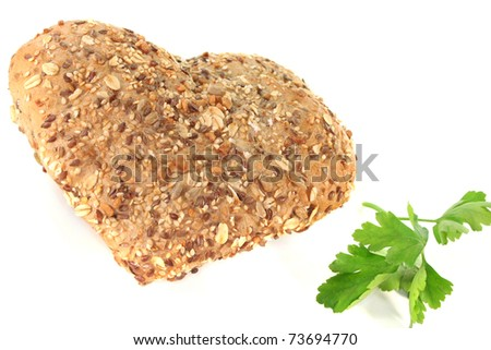 Whole grain bread into heart shape with parsley on a white background
