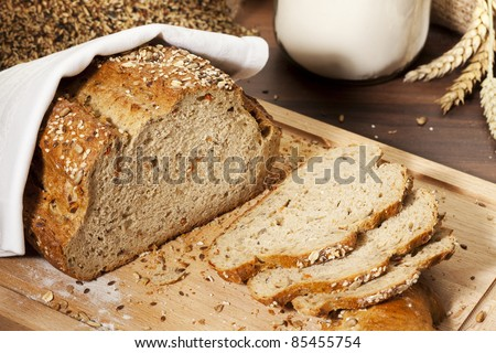 whole grain bread loaf and slices on cutting board, grain and flour in background