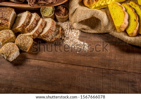 whole grain bread made with sesame seeds, sunflower seeds,  linsced, oatmeal, barley, rye, chia, pumpkin seed, poppy, nutmeg, with other breads and ingredients in background. top view lettering