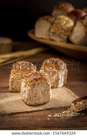 whole grain bread made with sesame seeds, sunflower seeds,  linsced, oatmeal, barley, rye, chia, pumpkin seed, poppy, nutmeg, on rustic wooden table with other breads and ingredients in background.