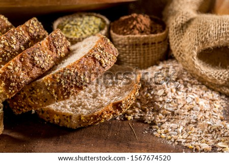 whole grain bread made with sesame seeds, sunflower seeds,  linsced, oatmeal, barley, rye, chia, pumpkin seed, poppy, nutmeg, with other breads and ingredients in background.