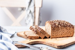 Whole grain bread on white, wooden table