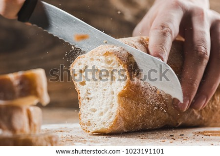 Whole grain bread put on kitchen wood plate with a chef holding gold knife for cut. Fresh bread on table close-up. Fresh bread on the kitchen table The healthy eating and traditional bakery concept - Shutterstock ID 1023191101
