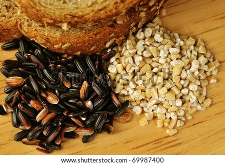 Whole grain goodness.  Close up image of whole wheat bread, steel cut oats, and black (mahogany) rice on wood cutting board.