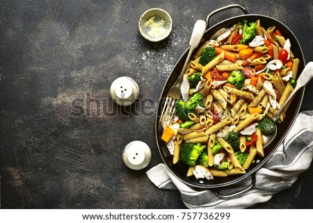 Whole grain penne pasta with vegetables and roasted chicken in a skillet over dark slate or metal background.Top view.