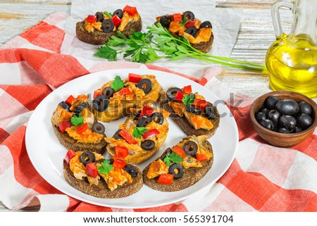 whole grain rye Crostini with pieces of mackerel fish, rings of black olives, red bell pepper on white plate on kitchen cloth, bottle with cooking oil and parsley on wooden background, close-up