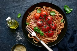 Whole grain spaghetti pasta with grilled cherry tomato in a black bowl over dark slate, stone or concrete background.Top view with copy space.