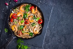 whole grain spaghetti pasta with shrimps and broccoli, top view, copy space