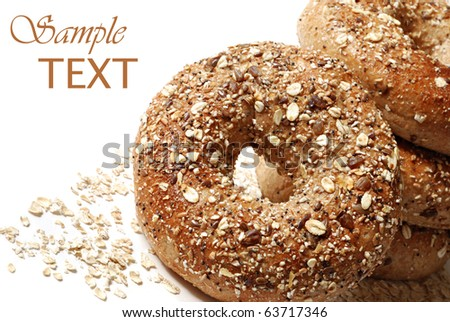 Whole grain wheat bagels with oat flakes on white background with copy space.  Macro with shallow dof.