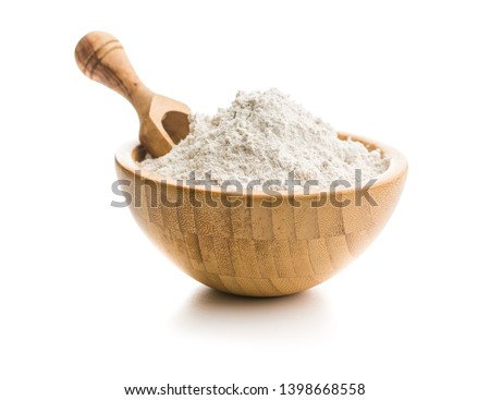 Whole grain wheat flour in bowl isolated on white background.