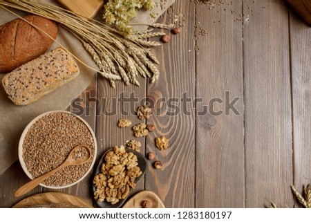 Whole grain, whole loaf and sliced pieces of multigrain bread contains whole grains (poppy, millet, flaxseed, pumpkin seeds, and sunflower seeds) isolated on dark wooden table with a copyspace. #1283180197