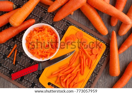 Whole, grated and chopped carrots. View from above. A lot of carrots are scattered on the table. Grated, chopped and whole carrots are needed for cooking. Carrots for diet and healthy eating.