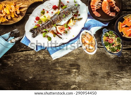 Whole Grilled Fish on White Platter Surrounded by Seafood Dishes on Rustic Wooden Table with Linen Napkins and Cutlery with Copy Space