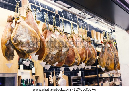 Whole ham hanging from the ceiling in a delicatessen shop.