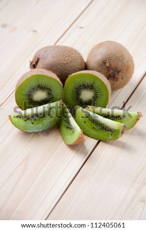 Whole kiwi fruit and his segments on wooden boards, vertical shot