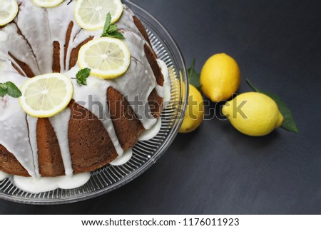 Whole lemon cream cheese bundt cake with slices of fresh lemons and mint on top. Extreme shallow depth of field with selective focus on cake.