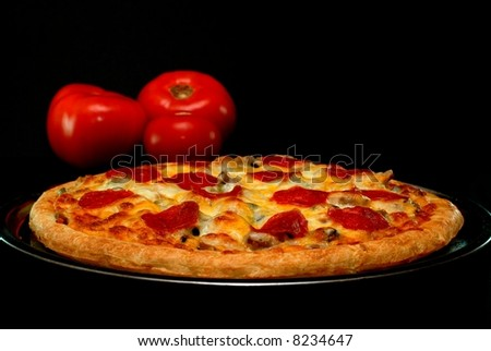 Whole pepperoni pizza with tomatoes in background.  Isolated on black background.